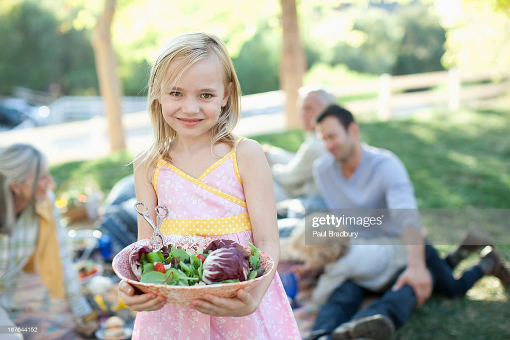 Girl carrying bowl of salad outdoors : Stock Photo