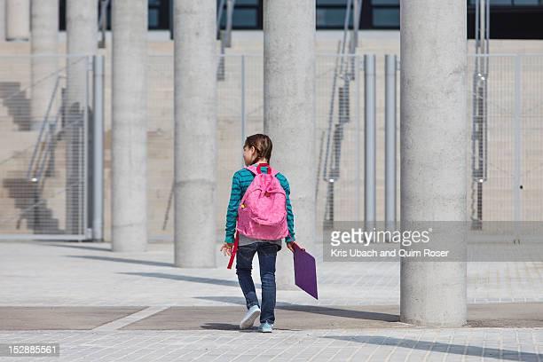 Girl carrying folder in courtyard