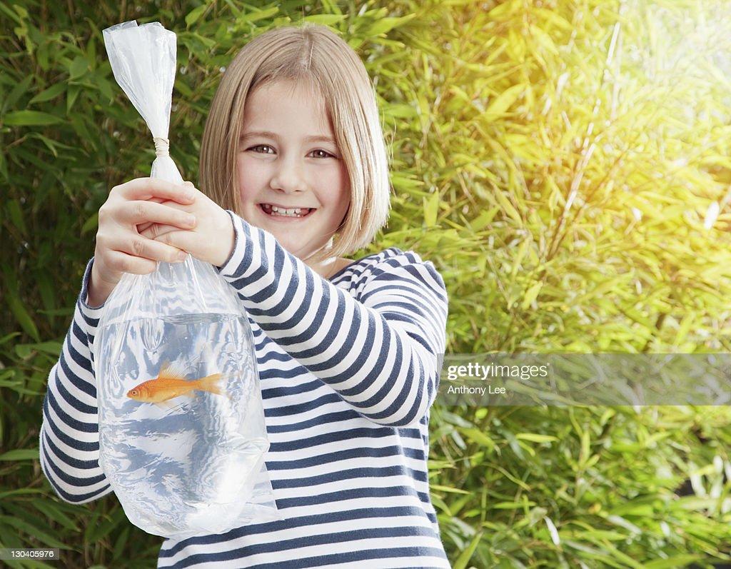 Girl carrying goldfish in plastic bag : Stock Photo