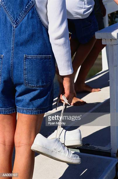 Girl Carrying Her Sneakers by the Laces
