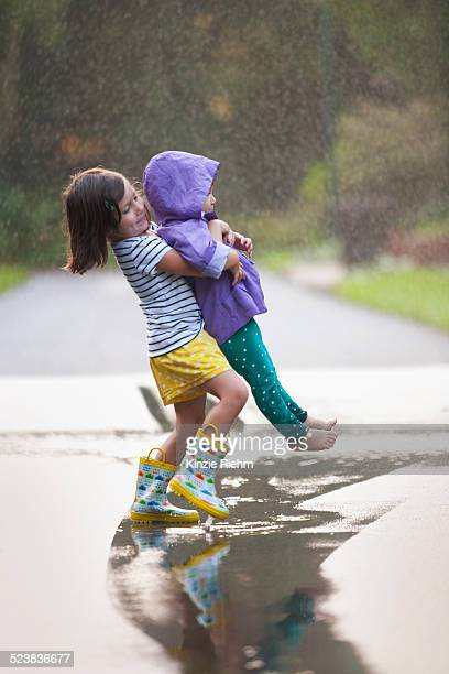 Girl carrying toddler sister through puddle on street