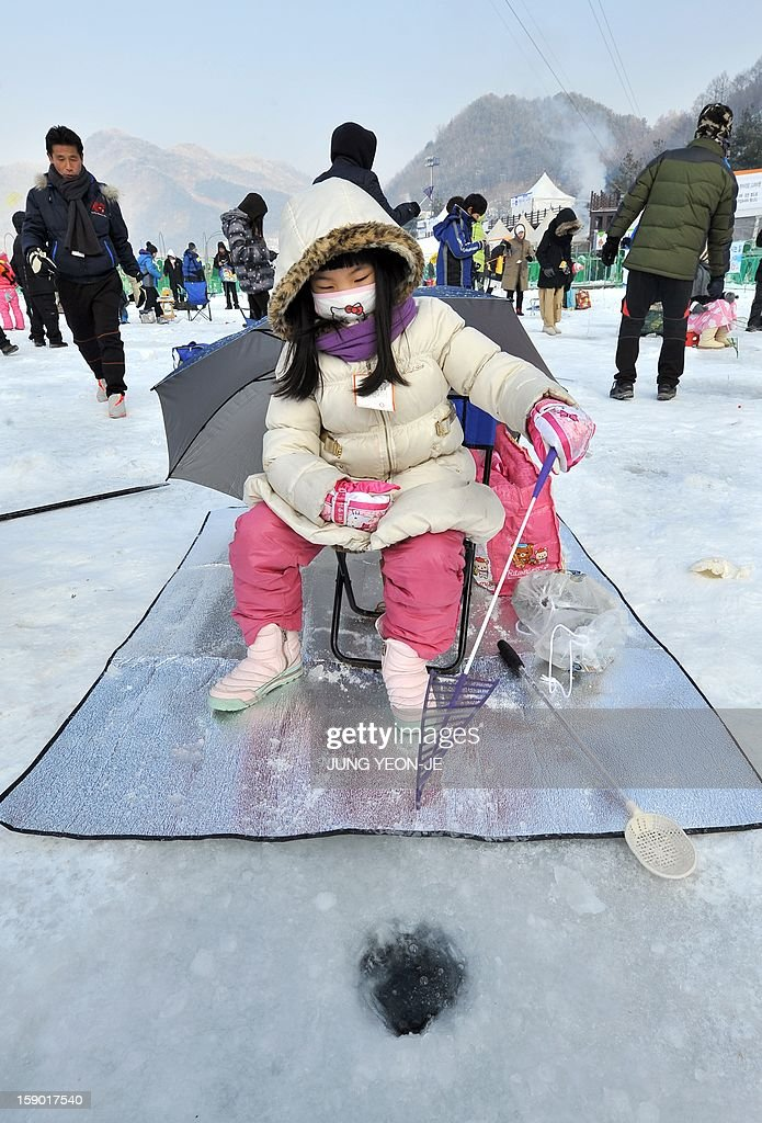 A girl casts a line through holes created in the surface of a frozen river during an ice fishing contest in Hwacheon, 120 kilometers northeast of Seoul, on January 6, 2013. The contest is part of an annual ice festival which draws over 1,000,000 visitors every year. AFP PHOTO / JUNG YEON-JE