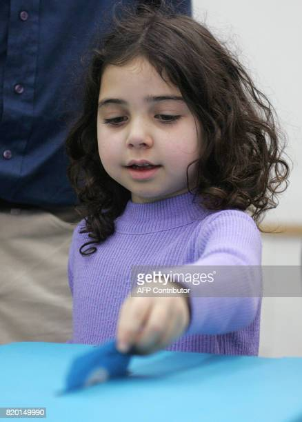 A girl casts her father's vote in the general elections 28 March 2006 at a polling station in Jerusalem Israel headed to the polls today in a...