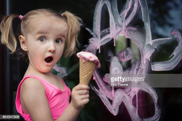 Girl (4-5) caught in the act, making a mess with pink ice cream