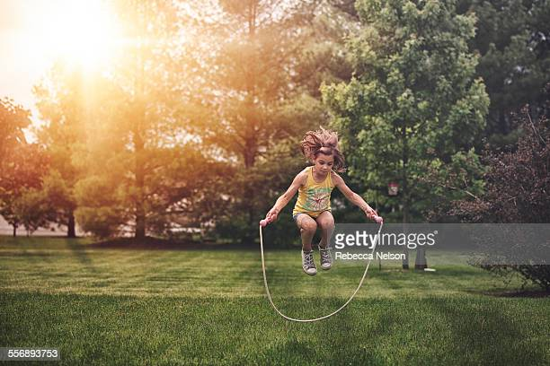 girl, caught mid air, jumping rope