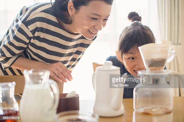 Girl challenging to drip coffee with mother