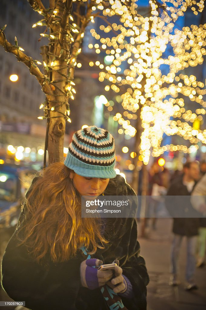 girl checking her phone, Winter in the city : Stock Photo
