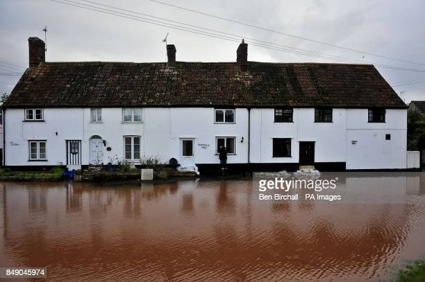 A girl checks through the window of a cottage on Cheats Road in the Somerset village of Ruishton near Taunton which has been flooded after the River...