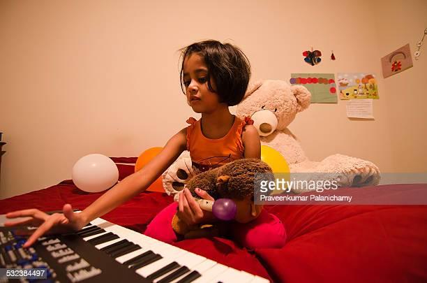 A girl child enjoying music in her bedroom
