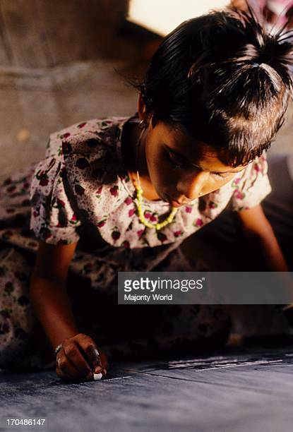 A girl child writes on a slate in the classroom of a non formal school setup by CONCERN in Khaliajuri Netrokona Bangladesh Education is fundamental...