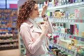 Girl choosing a perfume at store