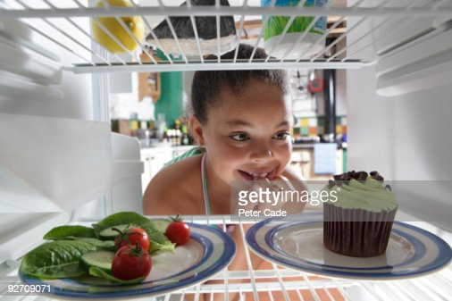 girl choosing between salad and cake : Stock Photo