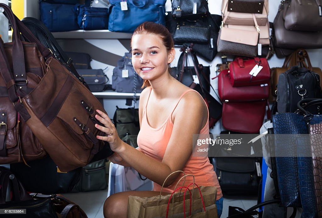 girl choosing handbag in store : Foto de stock