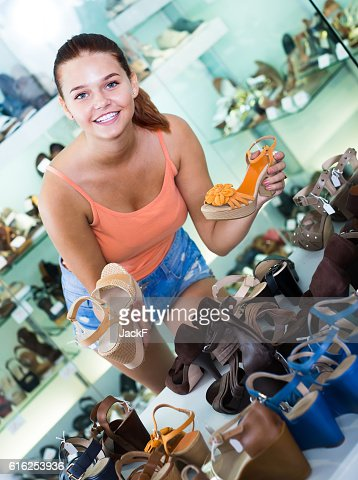 girl choosing pair of shoes in boutique : Stock Photo