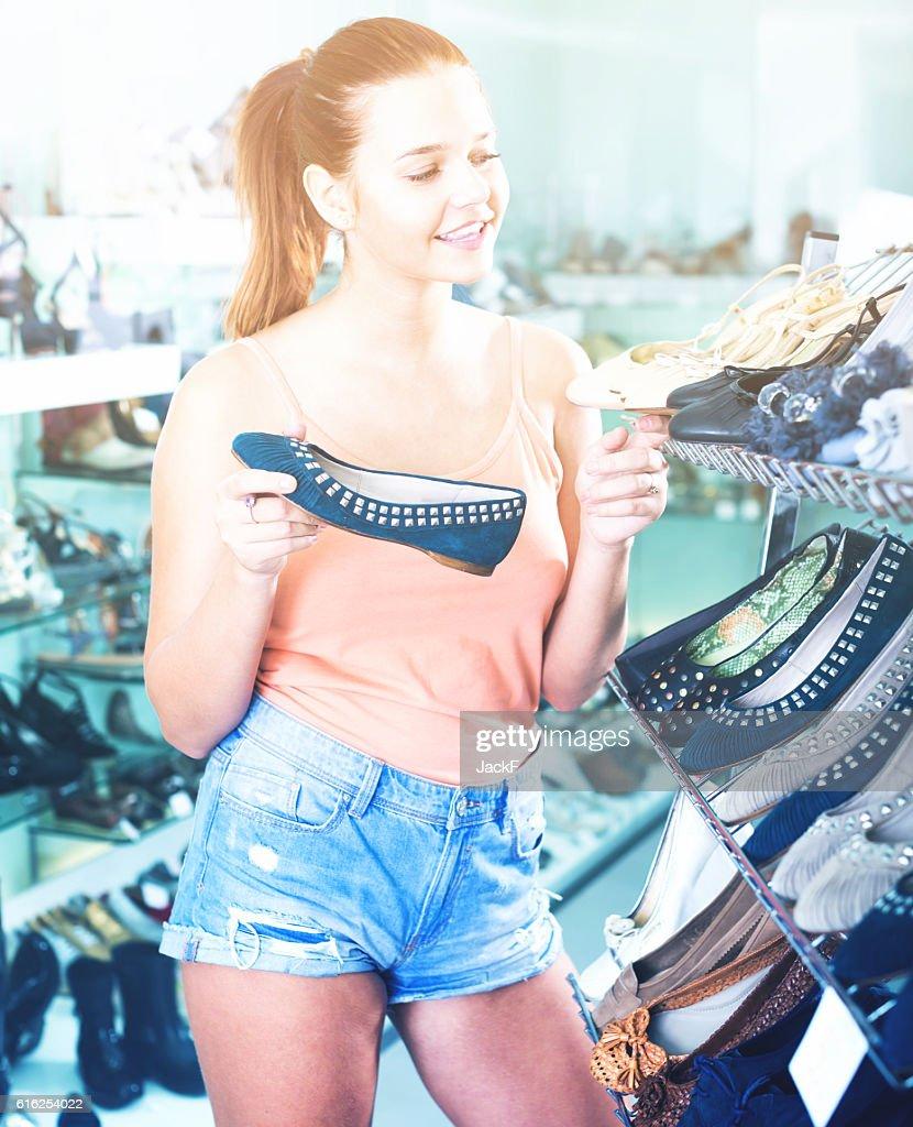 girl choosing pair of shoes in boutique : Foto de stock