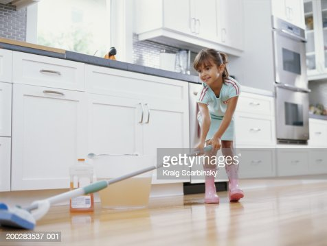 Girl (6-8) cleaning kitchen floor with mop, smiling, low angle view