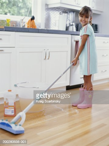 girl cleaning kitchen floor with mop smiling low angle view stock