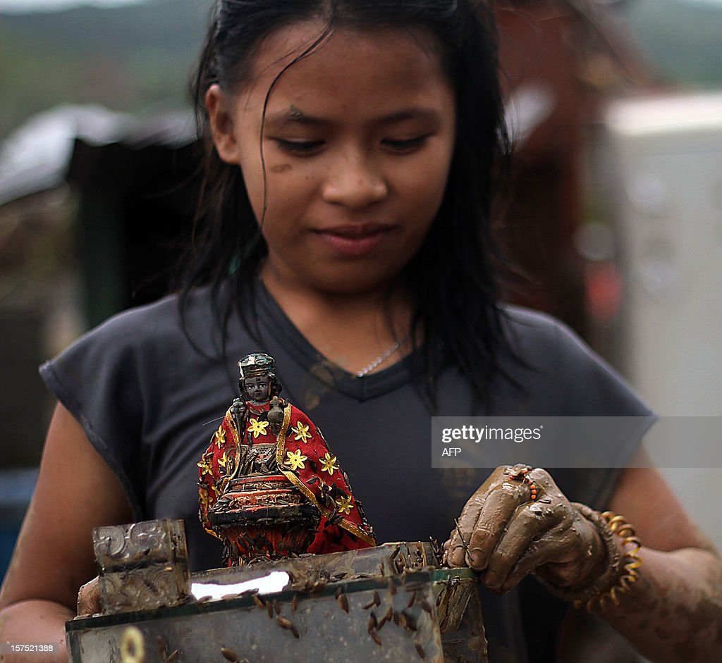 A girl cleans a religious statue of mud after landslides hit their home due to heavy rains brought about by Typhoon Bopha in Compostela town, Compostela Valley province, in southern island of Mindanao on December 4, 2012. Typhoon Bopha killed 43 people in one hard-hit Philippine town, local television station ABS-CBN reported from the scene. AFP PHOTO/Karlos Manlupig