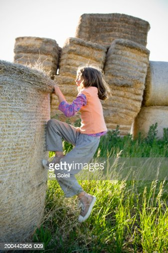 girl climbing hay bale side view stock foto getty images. Black Bedroom Furniture Sets. Home Design Ideas