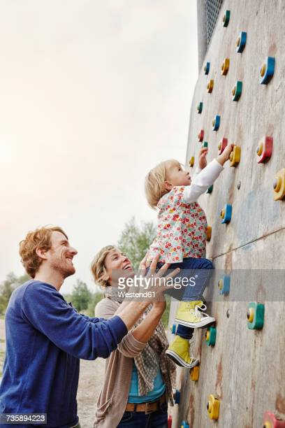 Girl climbing on a wall supported by parents