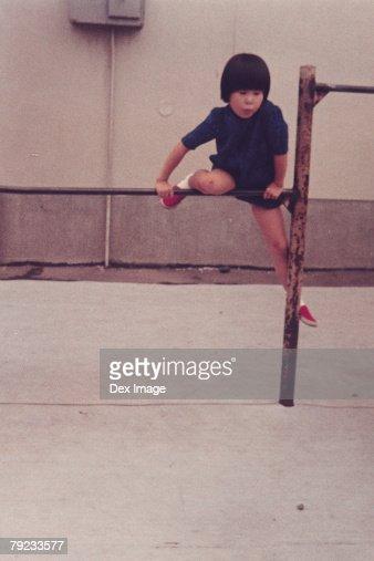 Girl climbing on monkey bar : Stock Photo