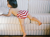 Girl (21-24 months) climbing on sofa, rear view