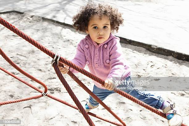 Girl climbing ropes in playground