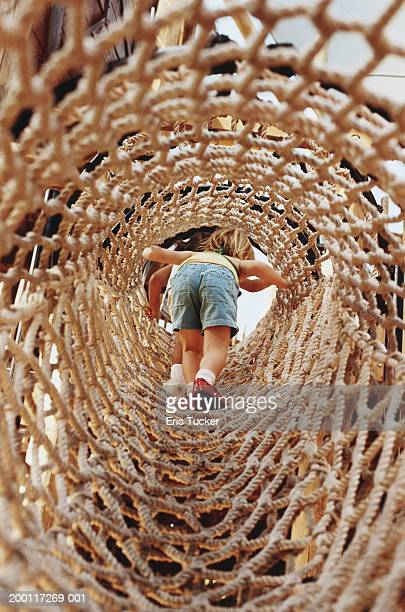 Girl (2-4) climbing through hanging rope tunnel, rear view