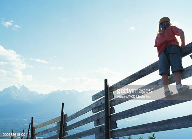 Girl (7-9) climbing wooden fence, mountains in background, rear view