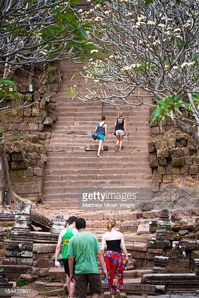 A girl climbs the temple stairs.