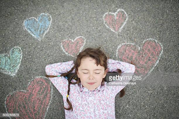 A girl closes her eyes, laying on a decorated road