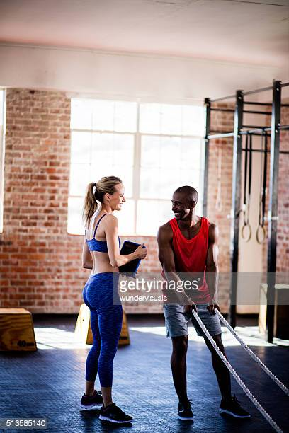 Girl coaching African descent man on ropes