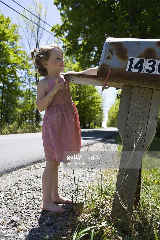Girl collecting mail from mailbox : Stock Photo