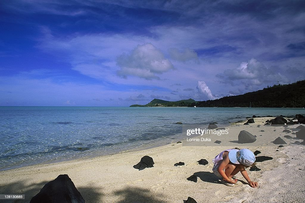 Girl collecting pebbles on the beach, Bora Bora : Stock Photo