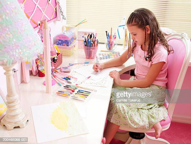 Girl (6-8) coloring at desk in bedroom, side view, close-up