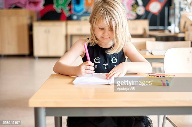 Girl coloring at desk in classroom