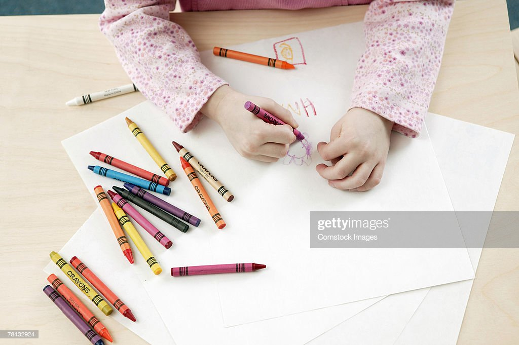 Girl coloring with crayons : Stock Photo