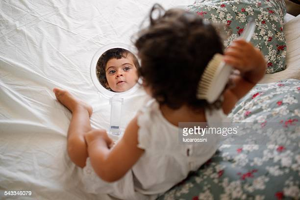 Girl (2-3) combing hair on bed with mirror