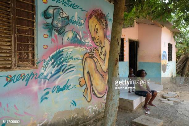 A girl combs her mother's hair outside their home sat next to a mural with writings in SpanishBantú language only spoken by Palenque de San Basilio...