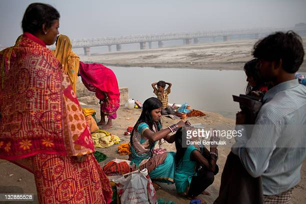 A girl combs her sisters hair after having bathed in the Ganges river during the Sonepur Mela on November 15 2011 in Sonepur near Patna India The...