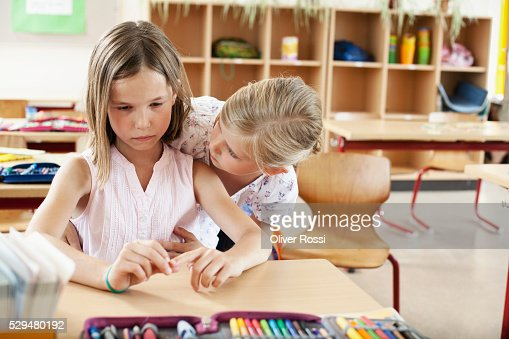 Girl comforting friend in classroom : Stock-Foto