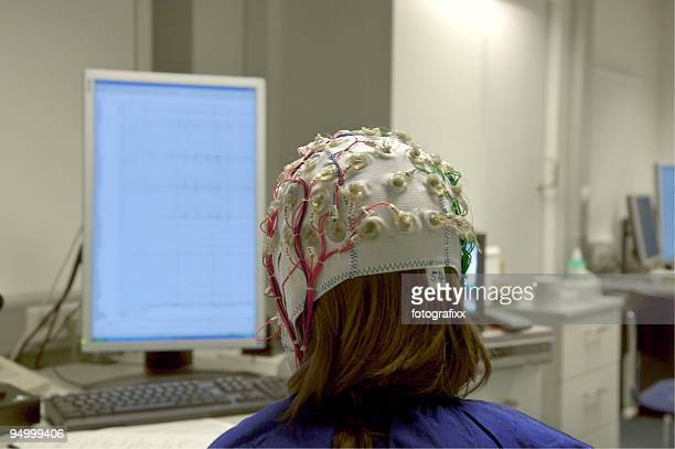 girl connected with cables for EEG in front of screen