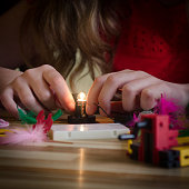 Female Child Wires a LIghtbulb Playing With Electronics Kit