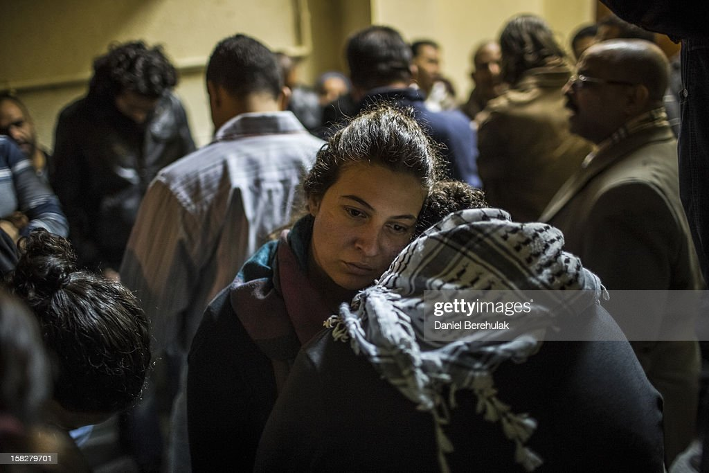 A girl consoles a friend as family and friends of killed journalist El-Hosseiny Abou-Deif wait for his body to be carried out from a morgue on December 12, 2012 in Cairo, Egypt. Egyptian journalist El-Hosseiny Abou-Deif who was hit in the head with a rubber bullet in last week's clashes at the presidential palace, was announced dead on Wednesday after spending a week in a coma. Anti-Morsi protesters were quiet after continued demonstrations across Egypt against the country's draft constitution, rushed through parliament in an overnight session on November 29. The country's new draft constitution, passed by a constitutional assembly dominated by Islamists, will go to a referendum on December 15.