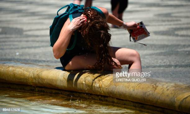 A girl cools herself in a fountain in Sevilla on June 10 2017 QUICLER