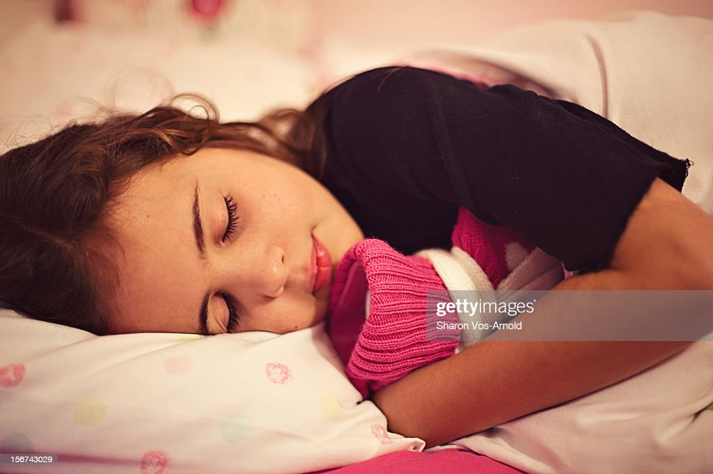Girl cosy in bed cuddling hot water bottle : Stock Photo