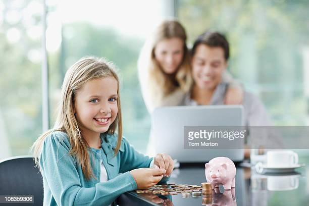 Girl counting coins with parents in background