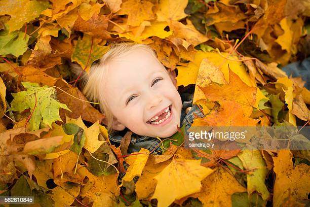 Girl covered in autumn leaves