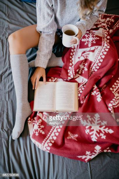 Girl covered with blanket reading a book in the bed