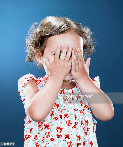 Girl (1-3) covering eyes with hands, close-up